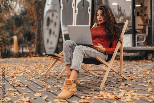 Beautiful woman in cozy outfit works at laptop while sitting on chair near cafe in autumn park Canvas