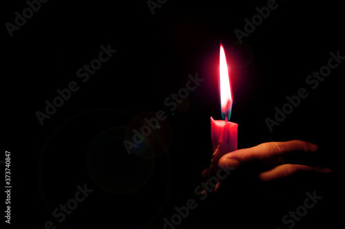 Fotografiet glare from a candle flame illuminates a woman's hand in a dark room, religion