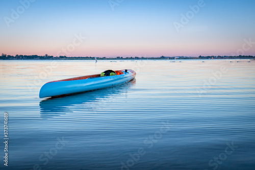 Foto long and narrow racing stand up paddleboard floating on a calm lake in Colorado,