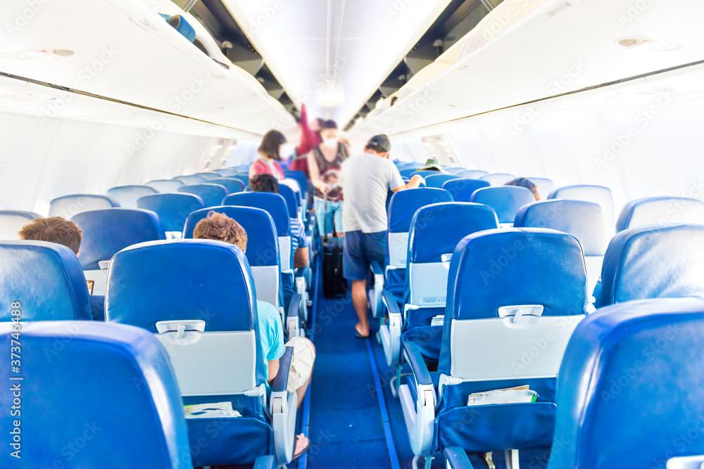 Fototapeta Empty plane interior with few people and stewardess during coronavirus pandemia
