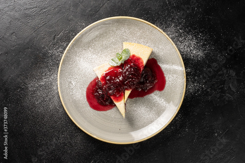 Two pieces of cheesecake on a round plate drizzled with strawberry jam and garni Tableau sur Toile
