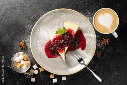 A cup of cappuccino and two slices of cheesecake on a round plate drizzled with strawberry jam and garnished with powdered sugar and mint leaves and scattered with white and brown sugar cubes Poster Mural XXL