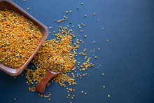 Bee Pollen In A Wooden Spoon Healthy Food Supplements. Dark Table Background. Ball Or Pellet Of Field-gathered Flower Pollen Packed By Worker Honeybees