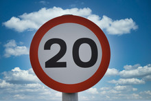 Twenty Miles Per Hour Speed Limit Sign, Isolated Against Blue Sky And White Clouds Background. Taken In UK.