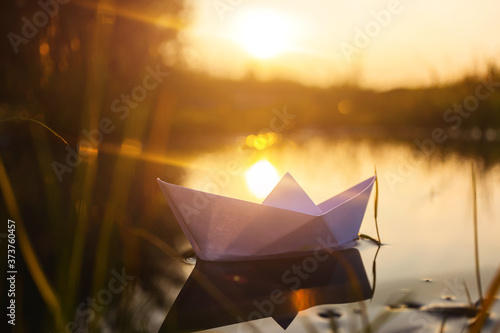 Obraz na plátně A paper boat floats on the water at dawn