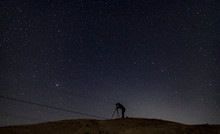 Silhouette Of Photographer Taking Pictures Of The Night Sky