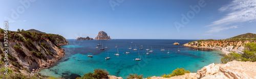 Fototapeta Panorama of beautiful bay Cala Hort with sea sailing yachts and the mountain Es Vedra