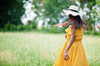 canvas print picture - Portrait of gorgeous african american woman 20s in wear in yellow dress and summer hat posing at green grass in park.
