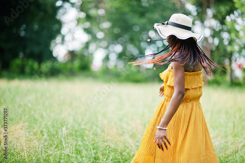 Portrait of gorgeous african american woman 20s in wear in yellow dress and summer hat posing at green grass in park Fototapeta