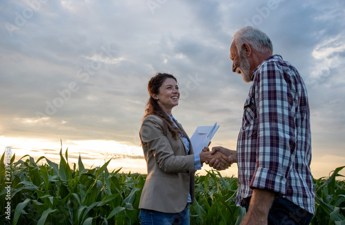 Farmer and business woman shaking hands in field Canvas Print
