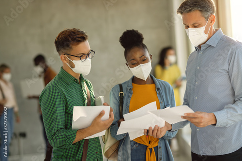 University professor and two students wearing face masks while communicating in a hallway Canvas