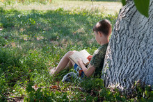 A Boy Of 9 Years Old Reads A Book Under A Tree In Nature. Digital Detox, Cottage Life