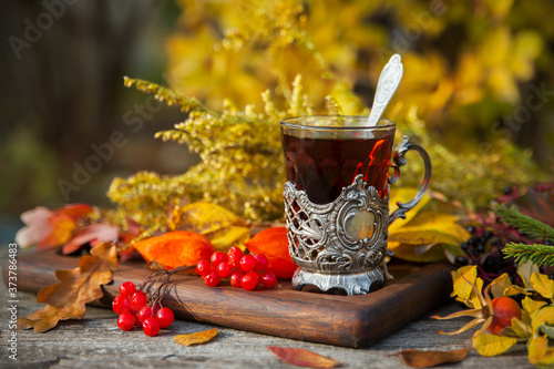 Photo A glass in the cup holder of hot tea on the table on an autumn afternoon