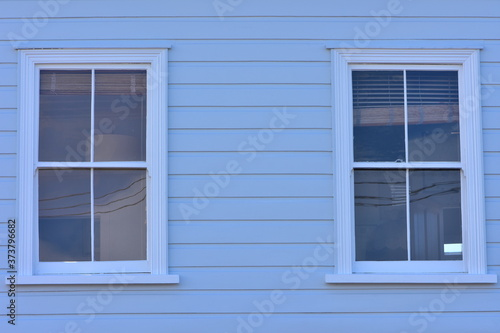 Vászonkép Vintage windows with four glass panes on wooden pale blue wall with weatherboard cladding
