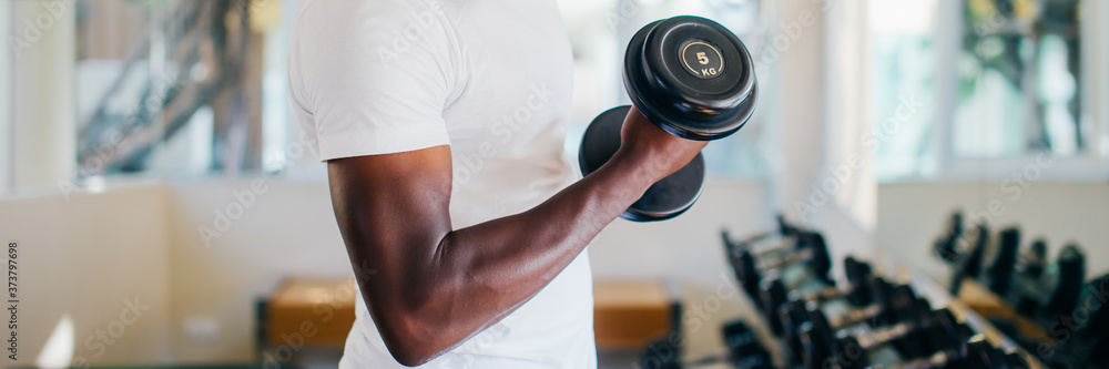 Fototapeta Young African American man standing and lifting a dumbbell with the rack at gym. Male weight training person doing a biceps curl in fitness center