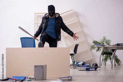 Young male burglar in the office Canvas Print