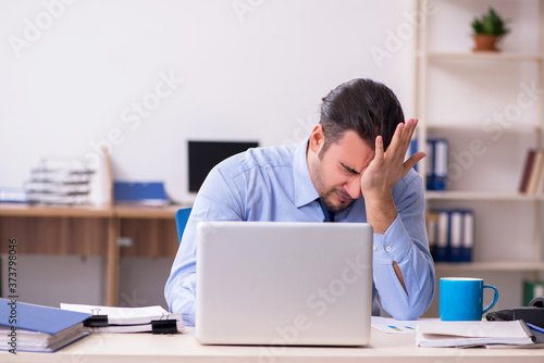 Sick male employee suffering at workplace Fototapete