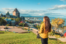Quebec City Canada Travel Destination. Asian Woman Tourist Walking Sightseeing Looking At View Of St Lawrence River And Chateau Frontenac Castle, Popular Destination For Autumn Traveling.