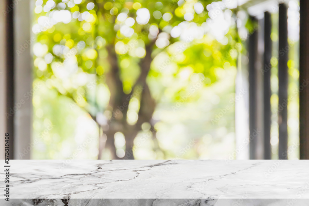 Empty white marble stone table top and blurred living room in home interior with green tree outside window background. - can used for display or montage your products.