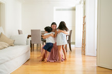 Laughing Mother Hugging Adorable Little Kids At Home. Happy Pretty Caucasian Mom Embracing Lovely Children, Smiling And Playing With Them. Motherhood, Leisure And Parenthood Concept