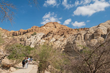 A Group Of Visitors On The Paved Handicapped Access Path Walking Toward The David Falls In The Ein Gedi Reserve In Israel With Mt Yishai In The Background