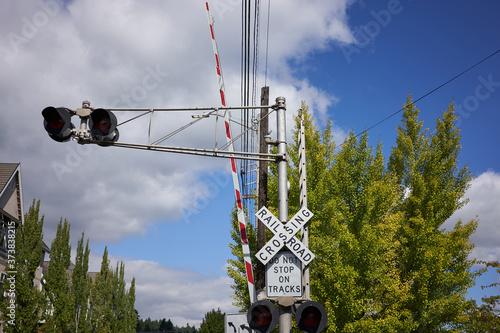 Railroad crossing gate with traffic lights warning signs. Tapéta, Fotótapéta