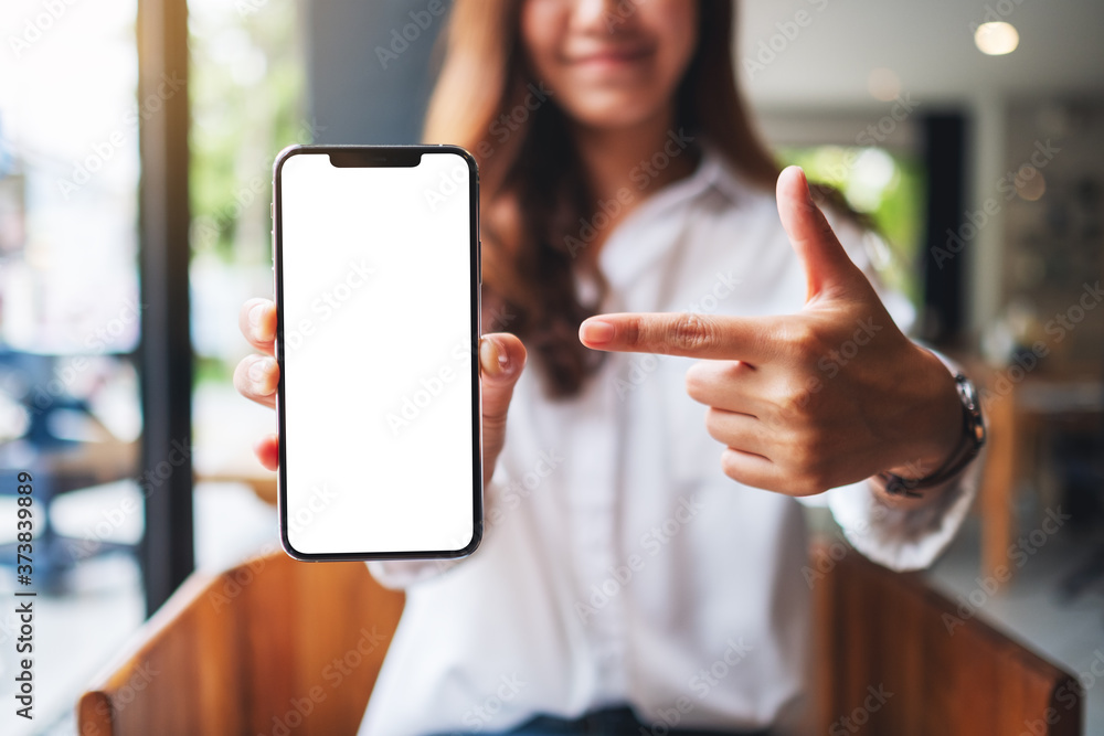 Fototapeta Mockup image of a beautiful woman pointing finger at a mobile phone with blank white screen