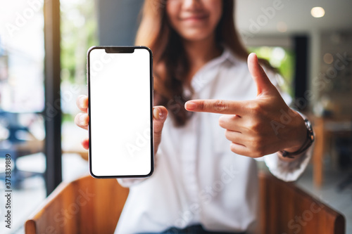 Fotografía Mockup image of a beautiful woman pointing finger at a mobile phone with blank w