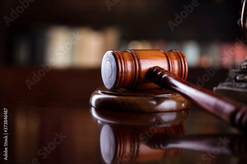 Judge's gavel on brown shining table and bookshelf background Canvas
