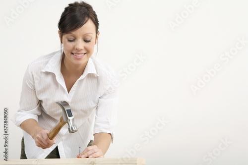Fototapeta Woman hammering nail into wood