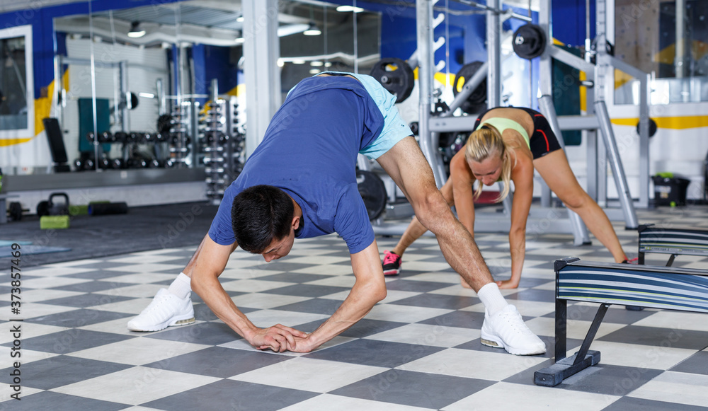 Fototapeta Young fit man and woman stretching before training workout at gym
