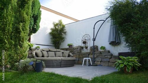Foto Gartenterrasse mit Loungegruppe in einer Gartenecke mit Säulen-Faulbaum und umge