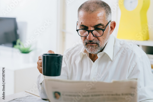 Fotografia middle aged man reading newspapers while having breakfast at home
