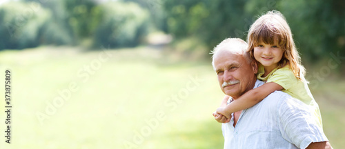 Fotografiet Little child girl hugs grandpa On Walk in the summer outdoors
