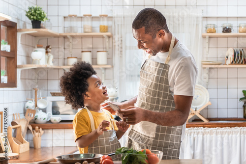 Fotografia African American Father and son laughing while cooking in kitchen