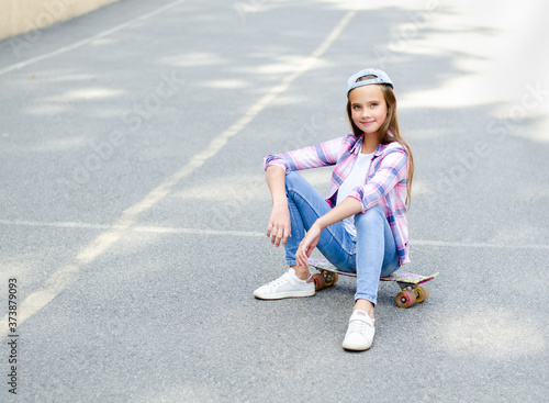 Valokuvatapetti Smiling cute little girl child in cap sitting on a skateboard