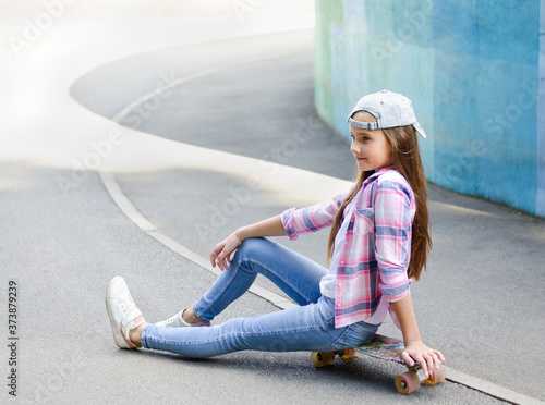 Valokuva Smiling cute little girl child in cap sitting on a skateboard