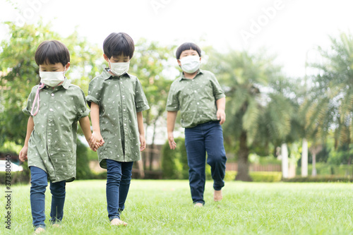 Photo 3 brothers are walking and playing in the garden in the evening..