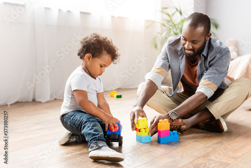 Fotografija young african american man playing with building blocks on floor with little son