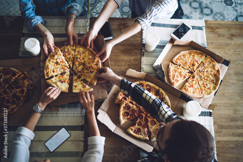 Fototapeta People together grabbing slices of pizza from box at table