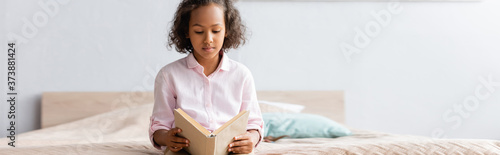 Tela horizontal image of focused african american girl in white shirt reading book wh