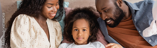 Fotografija panoramic crop of african american child lying in bed and looking at camera near
