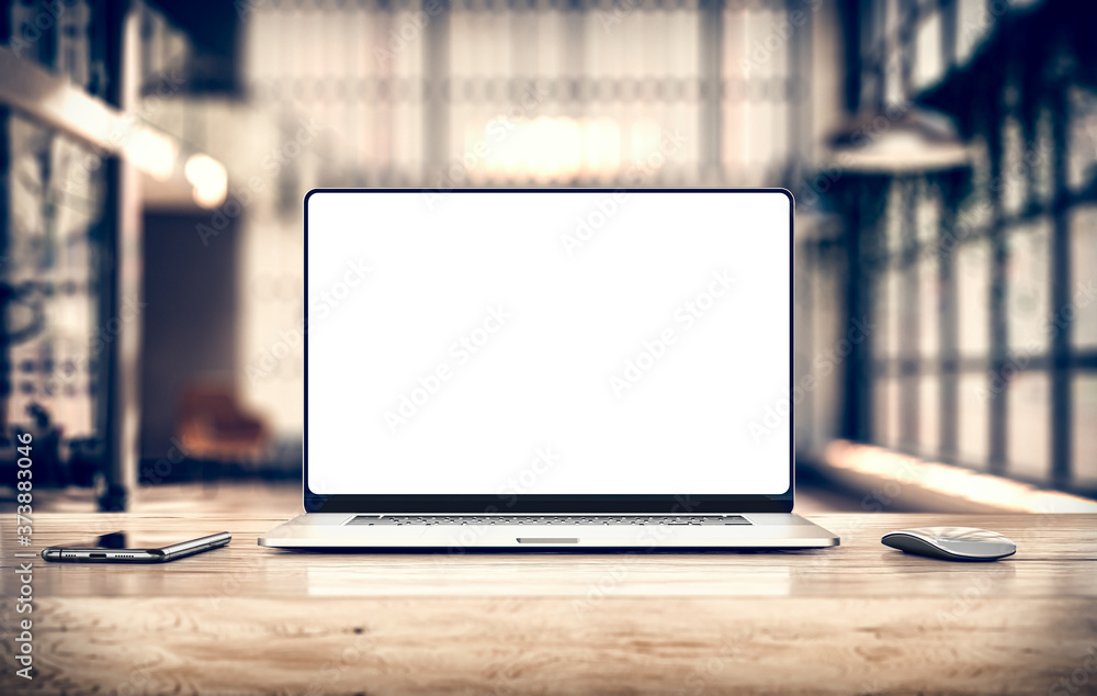Fototapeta Laptop with frameless blank screen mockup template on table in industrial office loft interior - front view