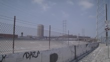 Wire Fence In An Industrial Area And Pan Right To An Electric Pylon And Train Tracks On A Clear Blue Day