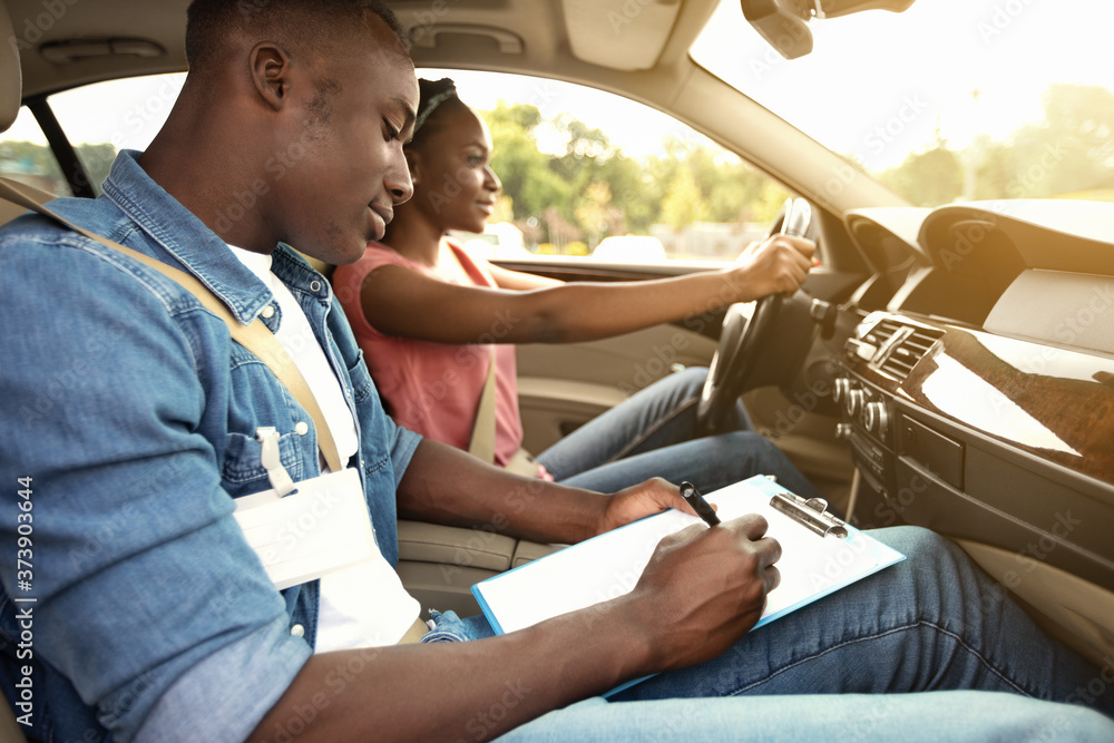Fototapeta Male instructor examining black woman driving car