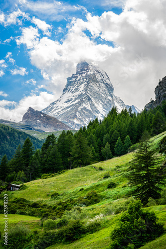 Fotografie, Tablou Vertical scenic view of the Matterhorn mountain summit with snow clouds blue sky