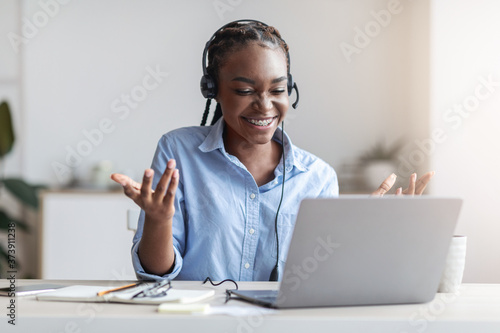 Obraz Video Conference. Friendly black woman having web call on laptop at office - fototapety do salonu