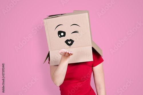 Person with cardboard box on its head and an amorous face expression blowing som Fototapet