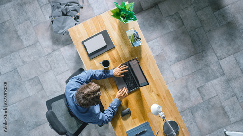 Fotomural Top View Shot: Businessman Sitting at the Wooden Desk Works on a Laptop in his Home Office