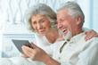 canvas print picture Close up portrait of happy senior couple using tablet